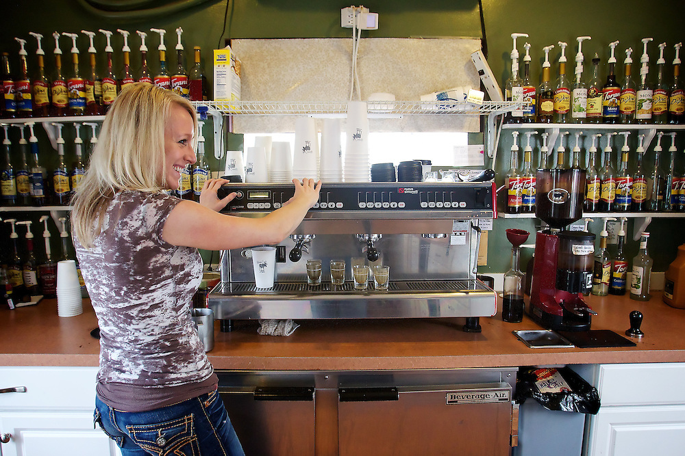Myria Ragland, owner of Moose Creek Coffee in Coeur d'Alene, talks with a customer at the drive-up window as she prepares a drink Thursday.