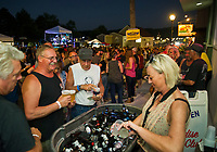 Paul Camire and Tom Duhamel buy ice cold beers from Cindy Mills outside Paradise Beach Club during Biketemberfest Saturday night.  (Karen Bobotas/for the Laconia Daily Sun)