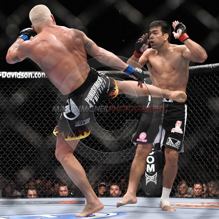 """LAS VEGAS, NEVADA, MAY 24, 2008: Tito Lyoto Machida (facing) jumps back from a kick thrown by Tito Ortiz during """"UFC 84: Ill Will"""" inside the MGM Grand Garden Arena in Las Vegas"""