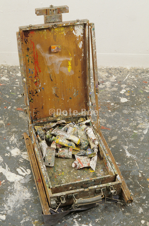 Easel and paint on a paint splattered floor