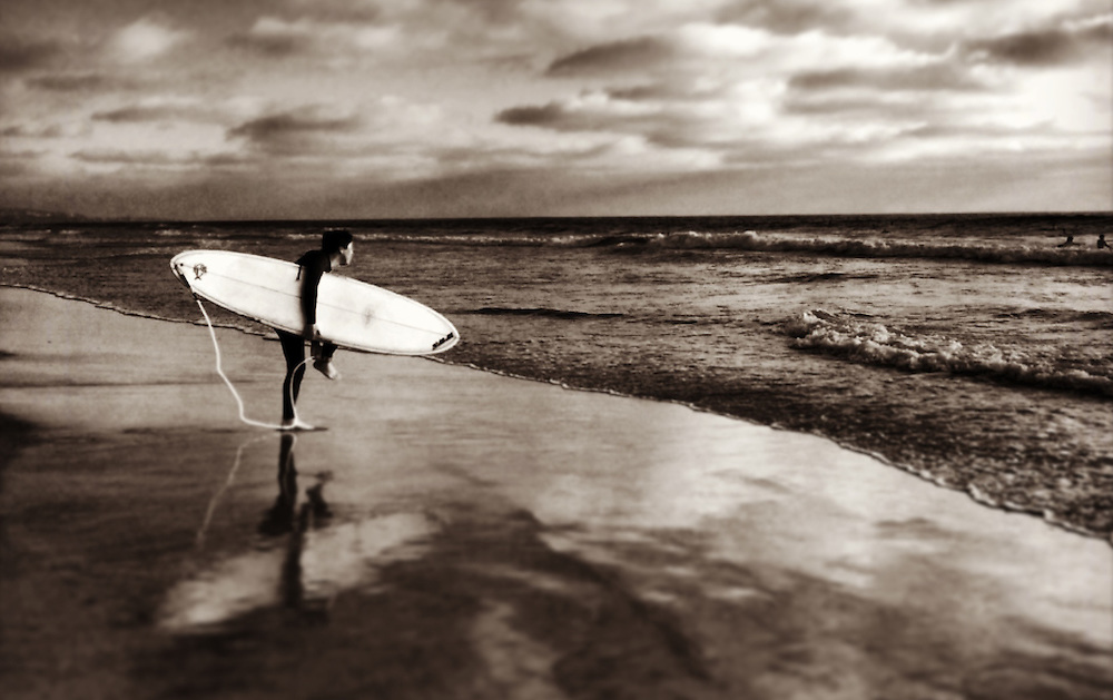 Surfer adjusts strap before heading out in Del Mar, CA