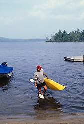 Man carrying a kayak out of a lake
