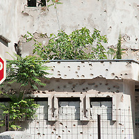 MOSTAR, BOSNIA AND HERZEGOVINA - JUNE 28:  A stop sign is seen in front of a concrete wall damaged by bulletts from the 1993 war is seen on June 28, 2013 in Mostar, Bosnia and Herzegovina. The Siege of Mostar reached its peak and more cruent time during 1993. Initially, it involved the Croatian Defence Council (HVO) and the 4th Corps of the ARBiH fighting against the Yugoslav People's Army (JNA) later Croats and Muslim Bosnian began to fight amongst each other, it ended with Bosnia and Herzegovina declaring independence from Yugoslavia.  (Photo by Marco Secchi/Getty Images)