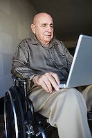 Elderly man in wheelchair using laptop