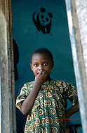 Young girl at the door of her house in a remote village of southeast Cameroon. WWF logo is visible in the background.