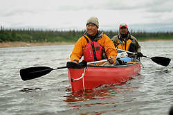 Richard Jeo, a scientist with the Nature Conservancy, front, and Dr. Sanjayan Muttulingam paddle  and fish with Dene First Nation youth down the Thelon river In the middle of the largest and most remote game sanctuary in North America, in the Northwest Territories, just south of the Arctic Circle. Its fate now hangs in the balance, protected on paper, but with little management, no money, and no voice for the Dene, its most ardent advocate for protection, while mining (for diamonds, gold, and uranium) threats, buoyed by recent prices, loom.  Dene youth have rarely been deep into the Thelon, yet the caribou is still their life blood, reverentially important.  These Dene are amongst the last hunter/gatherers in the Northern Hemisphere.   (Photo by Ami vitale)