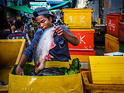 23 NOVEMBER 2017 - YANGON, MYANMAR: A worker packs fish in the San Pya Fish Market. San Pya Fish Market is one of the largest fish markets in Yangon. It's a 24 hour market, but busiest early in the morning. Most of the fish in the market is wild caught but aquaculture is expanding in Myanmar and more farmed fresh water fish is being sold now than in the past.    PHOTO BY JACK KURTZ