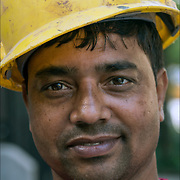 Portrait of Bangladesh American blue collar worker with yellow hard hat looking into the camera.