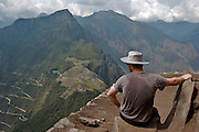 A tourist is admiring the lost Inca city of Machu Picchu, located in Cusco, Peru