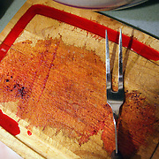 A bloody cutting board with utensil.