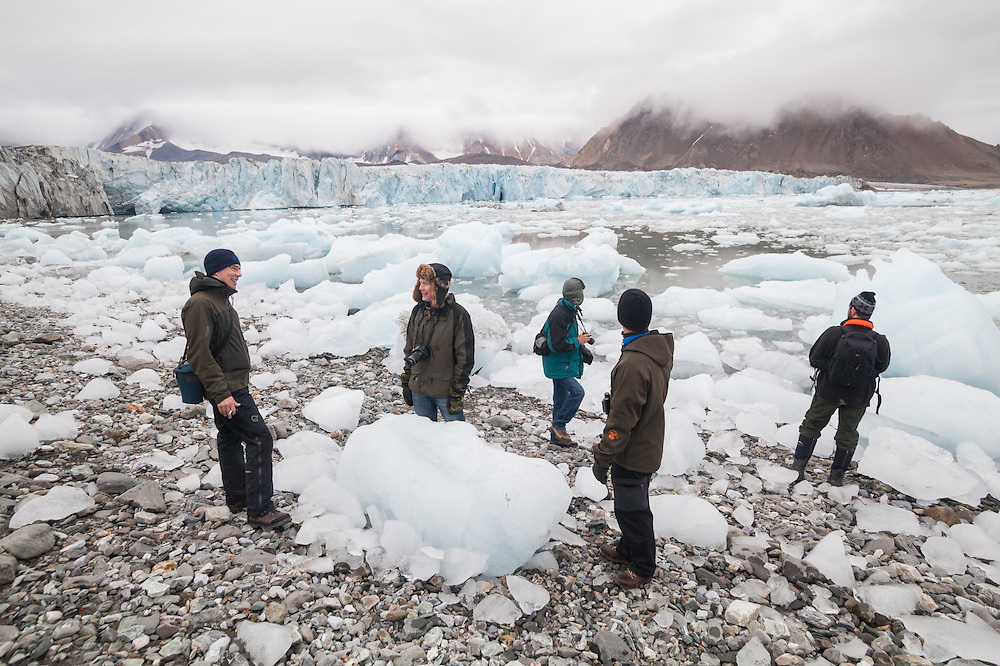 Men explore the calved icebergs filling the forebay of Hansbreen, Hornsund, Svalbard.
