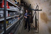 Nirojan Selvarasa holding a cross in a storage room in the workshop where maintenance work is carried out, in the crypt of the Cathedrale Notre-Dame de Paris, or Notre-Dame cathedral, built 1163-1345 in French Gothic style, on the Ile de la Cite in the 4th arrondissement of Paris, France. Photographed on 20th March 2019 by Manuel Cohen