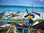 03 AUGUST 2017 - KUTA, BALI, INDONESIA:  Fishermen walk among the beached outrigger canoes on Jimbrana Beach in Kuta. The beach is close to the airport and a short drive from other beaches in southeast Bali. Jimbrana was originally a fishing village with a busy local market. About 25 years ago, developers started building restaurants and hotels along the beach and land prices are rising. The new emphasis on tourism is changing the nature of the area but the fishermen are still busy very early in the morning.    PHOTO BY JACK KURTZ