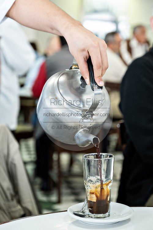 A waiter pours hot coffee into a glass at the iconic Gran Café de La Parroquia along the Malecon in Veracruz City, Mexico. The cafe is known for their long pours of hot milky coffee known as a lechero which they have served since 1808 and in their current form has operated continuously since 1926.