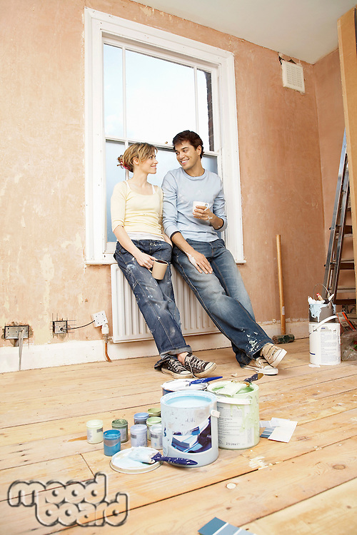 Couple taking a break from painting living room