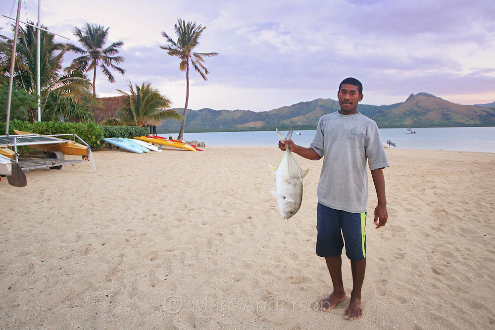 A Fijian man standing on a beach and holding a large fish..