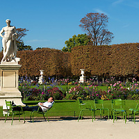 A man napping on chairs in the Tuileries Gardens.