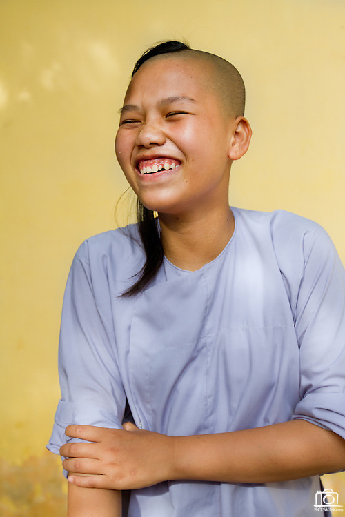 An intern, or nun in training, at the Chua Dieu Vien Pagoda laughs at me after I caught her wearing my sandals, Hue, Vietnam.  Photo by Stan Olszewski/SOSKIphoto