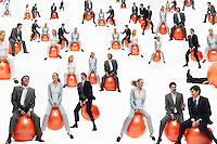 Large group of business people bouncing on inflatable balls studio shot