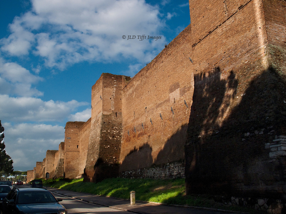 Aurelian Wall from outside San Sebastiano gate, with sun and shadow, bright blue sky and white clouds above.  One auto partly visible in the road.