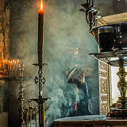Amid the smoke of burning incense, a Serbian Orthodox monk reads bible verses during afternoon liturgy at Zavala Monastery, Zavala Village, Herzegovina.