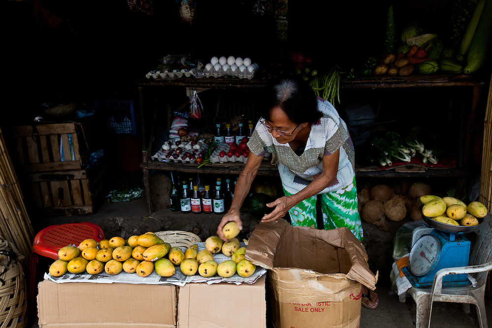 Woman puts out fruit for sale at corner market in Coron, Philippines. Copyright 2015 Reid McNally.