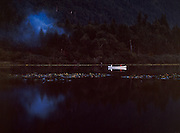 Silver Lake is a Whatcom County Park located near  the entrance to the Mount Baker National Forest on the North side.<br /> Dark image shot at dusk whit canoe stands out with smoke rising from the woods.