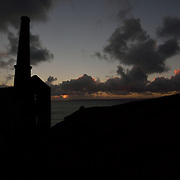 Wheal Prosper standing proud in the Cornish sky.<br /> <br /> Despite its name Wheal Prosper was not a hugely succesful mine, working for only six years between 1860-1866. It was intended to mine tin and copper from the Porthcew Lode<br /> <br /> The engine house is dramatically situated on the cliff tops of Rinsey over-looking Rinsey Cove and Porthcew Beach 3 miles from Portleven. Built of granite and killas slate taken from the local clifftops this fine engine house was home to a 30 inch pump.<br /> <br /> There were 3 shafts most notable of which is the now capped Michell's Whim shaft measuring an estimated 420ft in depth.<br /> <br /> The site has been under the stewardship of the National Trust since 1969.