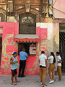 People including school children in uniform gather by a food kiosk in Havana Cuba