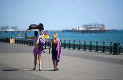© Licensed to London News Pictures. 03/07/2018. Hove, UK. A man uses his towel to shade himself form the sun while walking on the seafront at Hove, East Sussex on the south coast of England, as a heatwave continues across the UK. Photo credit: Ben Cawthra/LNP