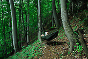 A hiker enjoys a peaceful moment in a hammock, Herculane Spa, Romania.
