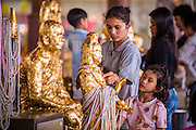 "12 OCTOBER 2012 - RAI KHRING, NAKHON PATHOM, THAILAND:  Thai Buddhists apply gold leaf to a Buddha statue to make merit at Wat Rai Khring in Nakhon Pathom province.  Wat Rai Khring was built in 1791. The Abbot at the time, Somdej Phra Phuttha Chan (Pook), named the temple after the district. When construction was completed, the Buddha image was brought from another temple and enshrined here. Later locals named the image ""Luang Pho Wat Rai Khing"". The Buddha image is of Chiang Saen style and is assumed to have been built by Lanna Thai and Lan Chang craftsmen.     PHOTO BY JACK KURTZ"