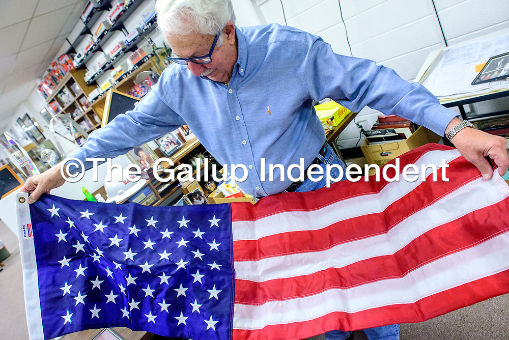 Joe DiGregorio unfurls a flag gifted from longtime friend former New Mexico Senator Domenici in Gallup Wednesday.