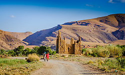 Two Berber women walk passed a ruined Kasbah in the M'Guin Gorge in southern Morocco<br /> <br /> (c) Andrew Wilson | Edinburgh Elite media