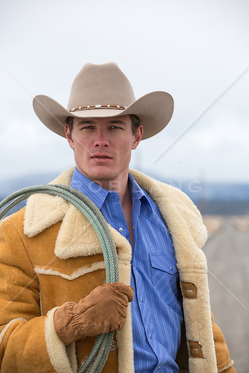 cowboy on a dirt road holding a lasso