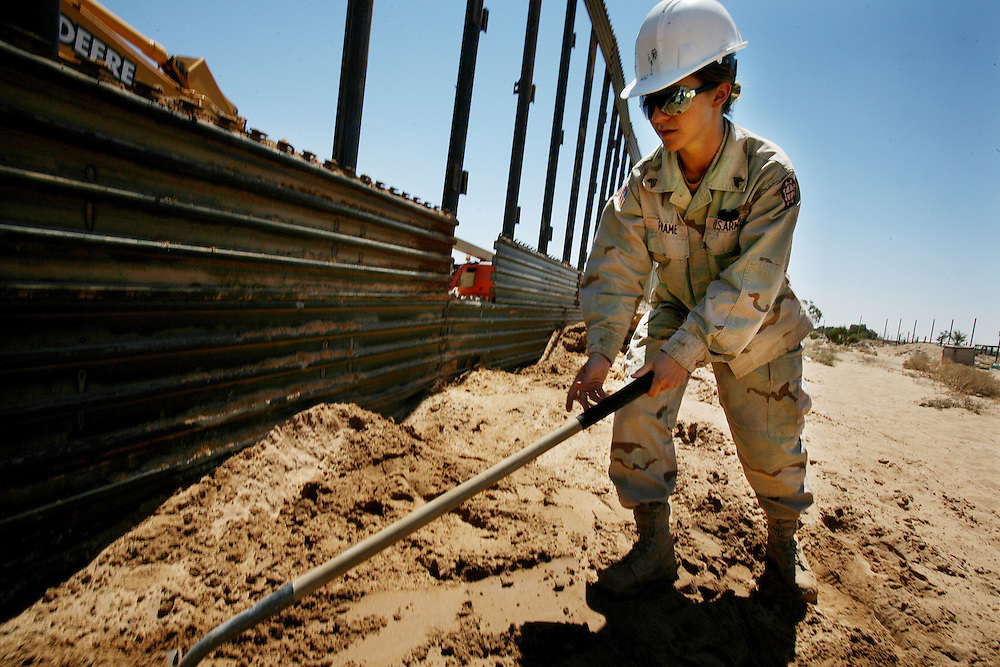 San Luis, AZ-June 15, 2006:  Sgt. Tina Frame, with the Utah National Guard shovels sand in place while helping to construct a portion of border wall in San Luis, AZ on Thursday, June 15, 2006.(Photo by Sandy Huffaker/The New York Times)