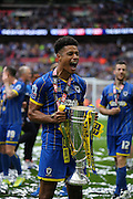 AFC Wimbledon striker Lyle Taylor (33) cheering with the trophy during the Sky Bet League 2 play off final match between AFC Wimbledon and Plymouth Argyle at Wembley Stadium, London, England on 30 May 2016.