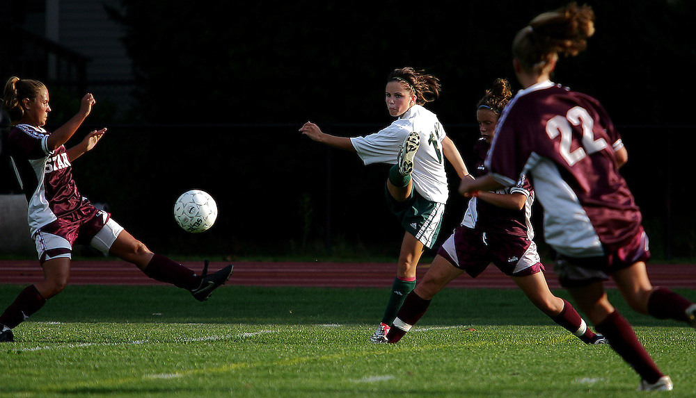 (100407  Attleboro, MA)  Bishop Feehan High School's Jessica Miller, #12, kicks the ball past Bishop Stang High School's players during their game Thursday afternoon.