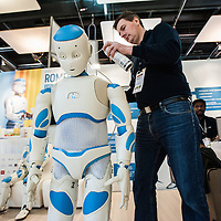 Lyon, France - 19 March 2014: Kristian Kassow of Aldebaran Robotics performs some early morning maintenance at Romeo Project Robot at Innorobo 2014, the 4th international trade show on service robotics.