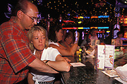 A couple cuddle at the Neon Bar on the cruise ship Ecstasy, en-route from Miami to Cancun in Mexico, on 15th May 1996, in Miami, Florida, USA. The Neon Bar features an enormous circular piano which doubles as a bar for those who like to sing along and neon artwork is lit behind the females, one the shape of another cocktail glass. Carnival's ships are known for their Las Vegas decor and entertainment. The cruise line calls its ships The Fun Ships and the MS Ecstasy is a Fantasy class cruise ship featuring two pools, whirlpools, a variety of dining options, nightclubs, a casino, and duty-free shopping.