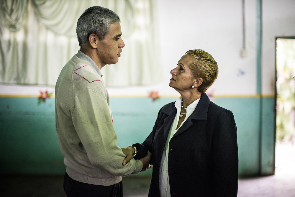 BARQUISIMETO, VENEZUELA - JULY 29, 2016: Mario Carrusí, 41, talks with head nurse,  Évila García in the hospital rec center. Mr. Carrusí is a schizophrenic who has also been diagnosed with mystical religious delusions. In 1998, before he was diagnosed, he killed his mother by decapitating her.  The nursing staff at the hospital fears that he could become violent again because he does not always have all the medications that he needs.  Carrusí has since become a devout evangelical Christian. PHOTO: Meridith Kohut for The New York Times.