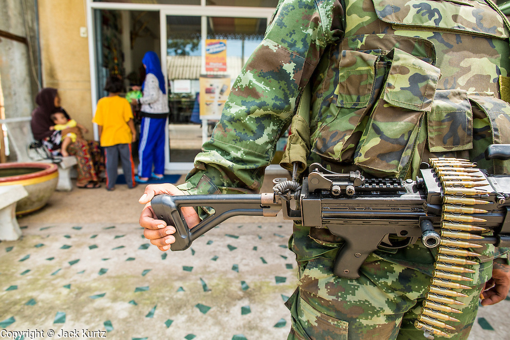 "25 OCTOBER 2012 - TAK BAI, NARATHIWAT, THAILAND: A soldier in the Royal Thai Army armed with MINI (machinegun) in front of a Muslim convenience store in Tak Bai, Thailand. The ""Tak Bai Incident"" took place on Oct. 25 in Tak Bai, Narathiwat, Thailand during the Muslim insurgency in southern Thailand. On that day, a crowd gathered to protest the arrest of local residents. Police made hundreds of arrests during the protest and transported the arrested to Pattani, about two hours away, in another province. They were transported in locked trucks and more than 80 people suffocated en route. This enraged local Muslims and shocked people across Thailand. No one in the Thai army accepted responsibility for the deaths and no one was ever charged. In the past, the anniversary of the incident was marked by protests and bombings. This year it was quiet. More than 5,000 people have been killed and over 9,000 hurt in more than 11,000 incidents, or about 3.5 a day, in Thailand's three southernmost provinces and four districts of Songkhla since the insurgent violence erupted in January 2004, according to Deep South Watch, an independent research organization that monitors violence in Thailand's deep south region that borders Malaysia.   PHOTO BY JACK KURTZ"