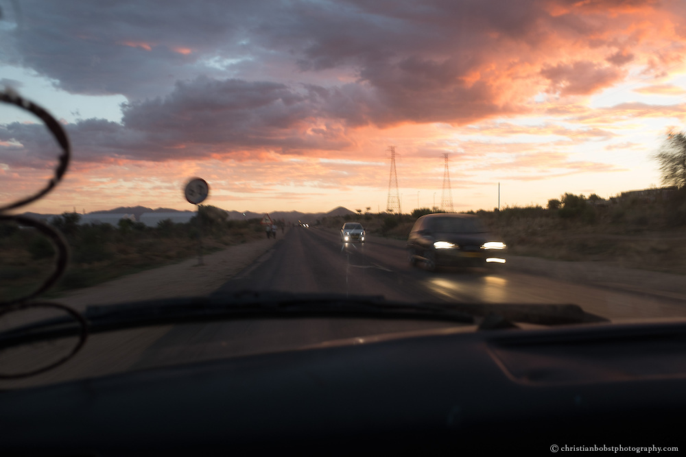 (2013) Father Hermann drives back home from the township while the sun sets.