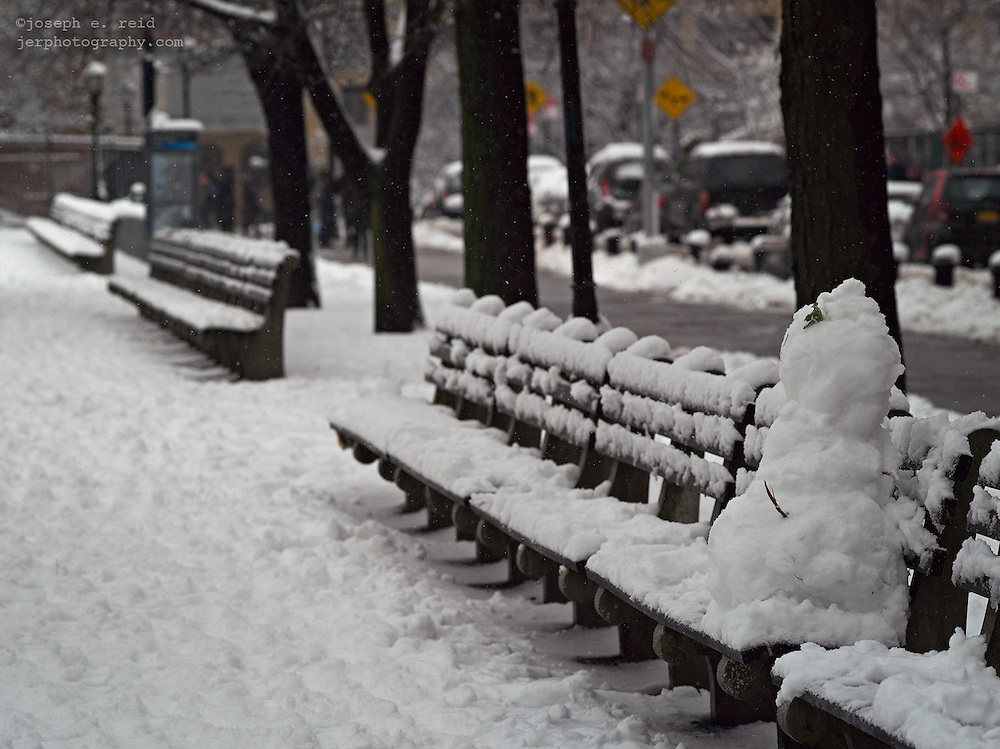 Snowman on park bench, Brooklyn, NY, US