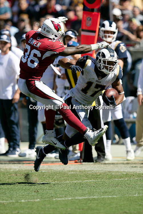Los Angeles Rams wide receiver Robert Woods (17) leaps and catches a third quarter pass for a gain of 21 yards and a first down at the Arizona Cardinals 21 yard line while covered by Cardinals defensive back Budda Baker (36) during the 2018 NFL regular season week 2 football game against the Arizona Cardinals on Sunday, Sept. 16, 2018 in Los Angeles. The Rams won the game in a 34-0 shutout. (©Paul Anthony Spinelli)
