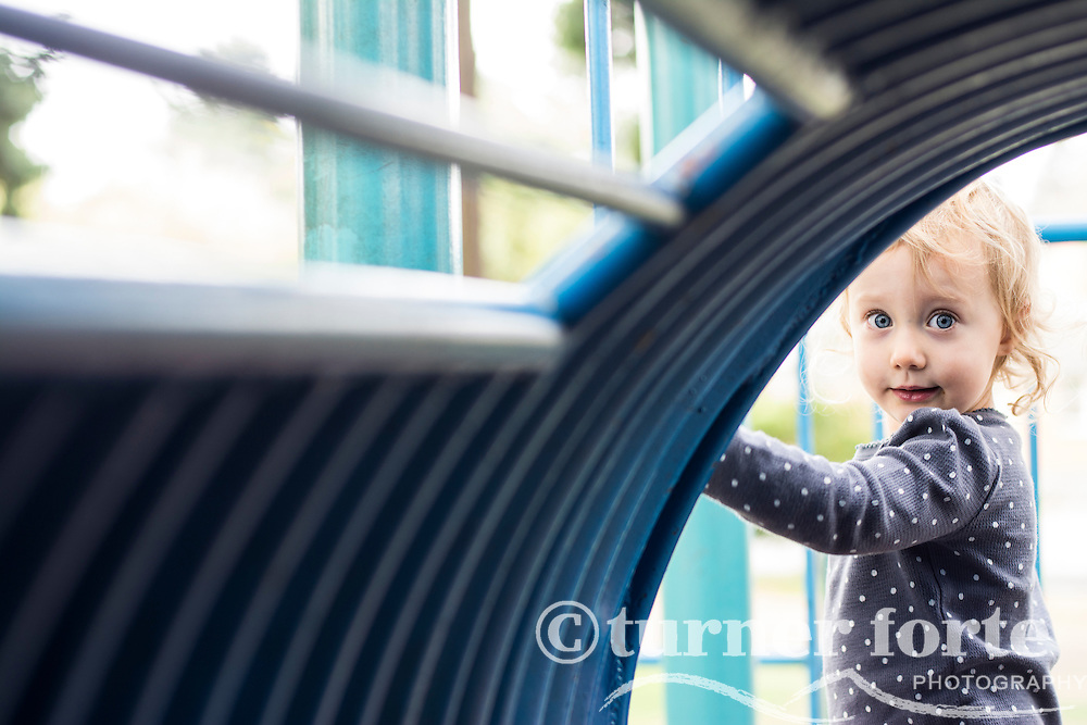 Toddler girl looks through blue tunnel at playground in Portland, Oregon.