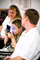 Corey Haas, 8, plays a video game while sitting between his parents, Nancy and Ethan, before entering surgery at the UPenn Medical Center in Philadelphia, PA on Thursday, September 25, 2008. Corey is sight-impaired and will undergo surgery injecting genetic material into his left eye in hopes of improving his vision.