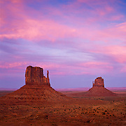 The pinkish hue of twilight lights up the clouds on Monument Valley Navajo Tribal Park