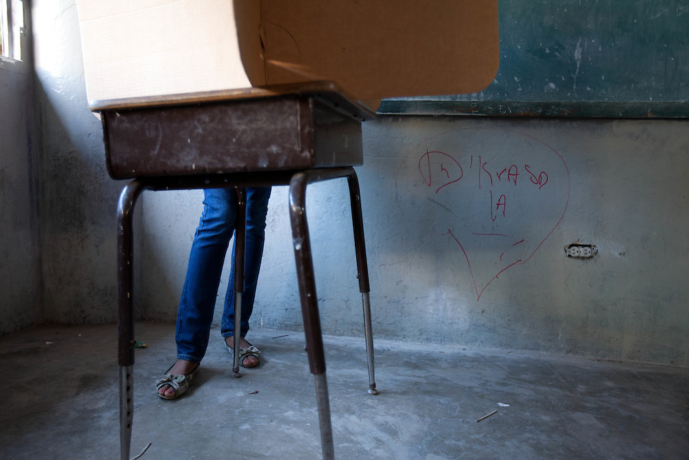 Voters fill out ballots in a school classroom.