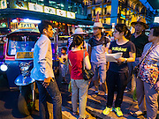 "28 JULY 2016 - BANGKOK, THAILAND:    Chinese tourists try to flag down a ""tuk-tuk"" or three wheeled taxi on Ratchadamri Road. Bangkok city authorities have promised to evict the street vendors on Ratchadamri by August 1, 2016.       PHOTO BY JACK KURTZ"